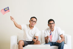 Malaysian men with Malaysia flag watching sports on tv. Young men watching live sport television program at home, waving Malaysia flag Stock Photo