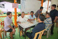 Malaysian men under a leantoo playing checkers Royalty Free Stock Image