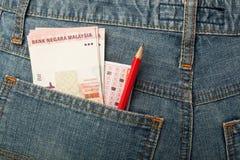 Malaysian money and lottery bet slip in pocket Royalty Free Stock Photo