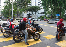 Malaysian motorcyclists stand at traffic lights Stock Images