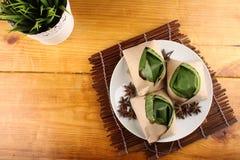 Malaysian nasi lemak. Traditional fresh Malaysian nasi lemak packed with banana leaf in wood background Stock Photos