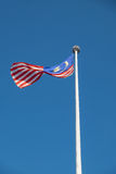 Malaysian national flag flying in wind on a pole with blue sky Royalty Free Stock Photos