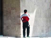 Malaysian Postman. A Malaysian postman leaving an office block complex after delivering postal mail in that building Royalty Free Stock Photo