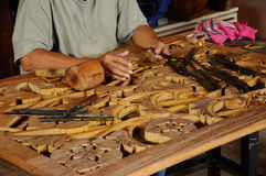 Malaysian traditional wood carving from Terengganu. TERENGGANU, MALAYSIA – NOVEMBER 2014: Malaysian traditional woof carving using traditional method on royalty free stock image