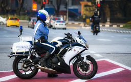 Malaysian Traffic Officer At Work. Kuala Lumpur, Malaysia: A traffic officer inspecting road in a motorcycle Royalty Free Stock Images