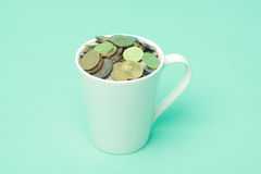 Malaysians coins in a white cup with terquoise background Royalty Free Stock Photo