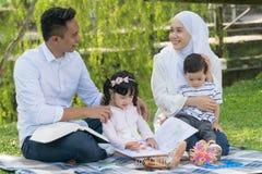 Malaysische Familie am entspannenden Park lizenzfreie stockfotografie