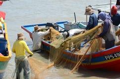 Malaysische Fischer, die ein Netz säubern Lizenzfreie Stockfotografie
