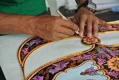 Malaysischer Drachenhersteller, der an einem Drachen in seiner Werkstatt arbeitet stockfotos