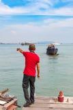 Malaysischer Mann zeigt etwas im Wasser Lizenzfreies Stockbild