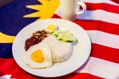 Malaysisches Frühstück - Nasi Lemak und der Tarik auf Malaysia-Flagge Stockfotografie