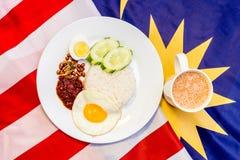 Malaysisches Frühstück - Nasi Lemak und der Tarik auf Malaysia-Flagge Stockfotos