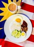 Malaysisches Frühstück - Nasi Lemak und der Tarik auf Malaysia-Flagge Lizenzfreie Stockfotos
