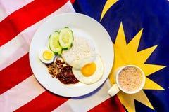 Malaysisches Frühstück - Nasi Lemak und der Tarik auf Malaysia-Flagge Stockbild