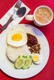 Malaysisches Lebensmittel - Nasi Lemak und schaumiges der Tarik auf einem roten backgr Lizenzfreie Stockfotografie
