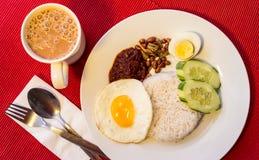 Malaysisches Lebensmittel - Nasi Lemak und schaumiges der Tarik auf einem roten backgr Lizenzfreie Stockbilder