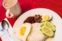 Malaysisches Lebensmittel - Nasi Lemak und schaumiges der Tarik auf einem roten backgr Stockfoto