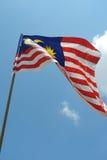 Malaysisk flagga i blåsig luft Arkivfoto