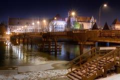 Malbork bij nacht met Kasteel Marienburg Stock Afbeelding