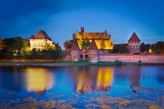 Malbork castle at dusk, Poland. Malbork castle in Poland at dusk with reflection in Nogat river Stock Photo