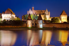 Malbork castle at night, Poland. Malbork castle in Poland at night with reflection in Nogat river Royalty Free Stock Photography