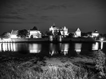 Malbork Castle by night. With reflection in Nogat river, Poland. Black and white image Stock Photography