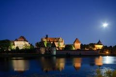 Malbork slott i Polen på natten med reflexion i den Nogat floden Arkivfoton