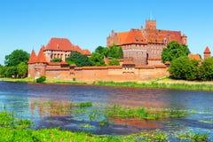 Malbork slott i sommarlandskap Arkivfoto