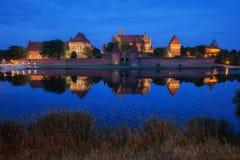 Malbork slott på natten i Polen Arkivbild