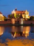 Malbork slott vid natt med reflexion i Nogat Arkivfoto