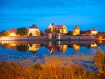 Malbork slott vid natt med reflexion i Nogat Arkivbild