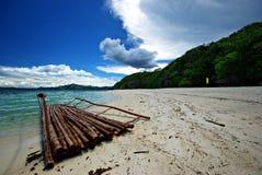 Malcapuya - Survivor. A makeshift raft along the powdery white shoreline of Malcapuya island in Coron Stock Photos