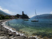 Malcesine at lake Garda, Italy. Shore of lake garda, with malcesine castle in the background and a anchored sailing ship in the foreground, on a sunny summer day Royalty Free Stock Photo