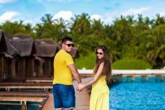 Maldiven, een paar die langs de brug door de villa's de lopen royalty-vrije stock fotografie