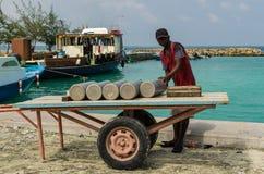 """MALDIVERNA †""""November, 2017: Bärande gascylinder för arbetare på en pir, tropisk Gulhi ö i Indiska oceanen, Maldiverna Arkivfoto"""