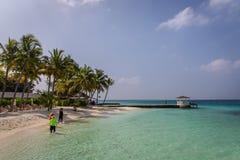 Maldiverna Februari 8th 2018 - turister som tycker om en lugna strand, blått vatten, tropiskt klimat, inga vågor i en dag för blå royaltyfri bild