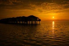 Maldiverna solnedgång med vattenvillakonturn Royaltyfri Bild