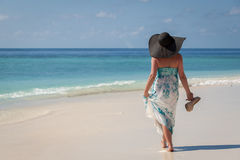 Maldiverna ung kvinna som promenerar stranden med sunhat och höga häl på handen royaltyfri foto