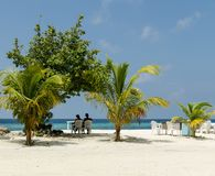 MALDIVES – November, 2017: Resting couple at tropical beach of Maafushi island, Maldives, Indian Ocean stock photography