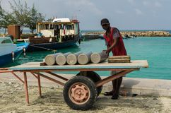 MALDIVES – November, 2017: Worker carrying gas cylinder on a pier, tropical Gulhi Island in Indian Ocean, Maldives Stock Photo