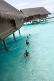 Maldives 24. Local madlivean's that clean up the barnacles on the stilts holding the villas up Stock Image