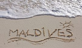 Maldives. Nice Maldives note written on white sand with ocean waves on background stock photos