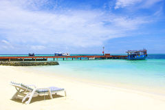 Maldives, beach with chair and dock with boat Stock Image