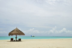 Maldives beach. View with umbrella and beach chair Stock Image