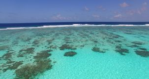 Maldives beautiful beach background white sandy tropical paradise island with blue sky sea water ocean 4k aerial. Drone flying flyover birds eye coral reef stock footage