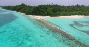 Maldives beautiful beach background white sandy tropical paradise island with blue sky sea water ocean 4k aerial. Drone flying flyover birds eye stock video