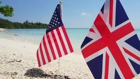 Maldives beautiful beach background white sandy tropical paradise island with blue sky sea water ocean 4k uk. Union jack us usa american flags stock video