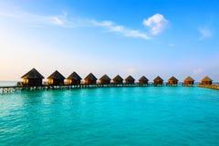 Maldives. Chalet en pilas en del agua los soles en ese entonces imagen de archivo