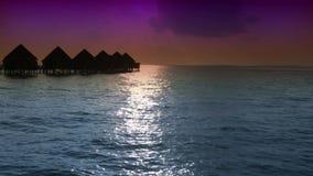 maldives Chambres sur des piles sur de l'eau le coucher du soleil alors clips vidéos