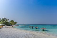 Maldives, Feb 3rd 2018 - Beach umbrellas at the shallow blue water with some divers enjoying the tropical weather of Maldives stock images